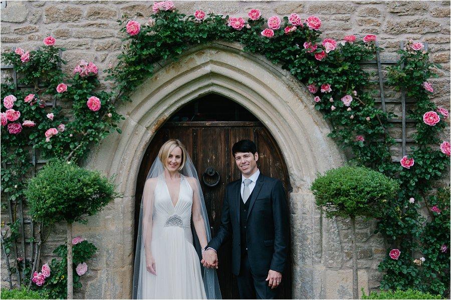 Wick Farm wedding photos couple holding hands under flowers