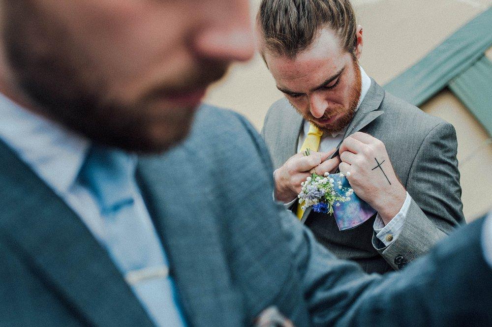 Wyldwoods groomsmen pinning flowers photo