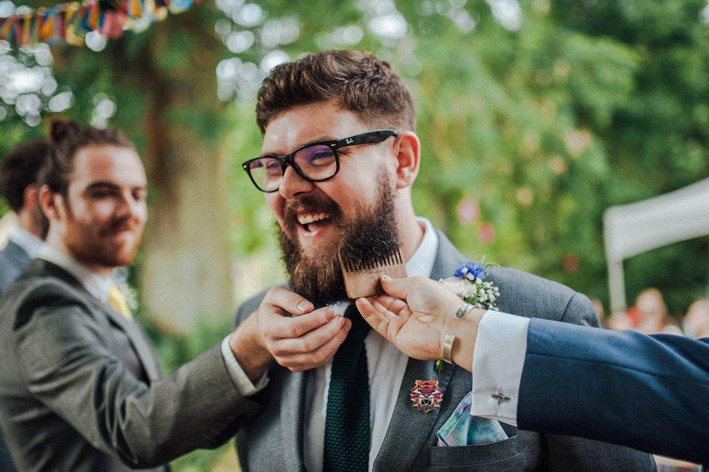 Wyldwoods groomsmen combing beard photo