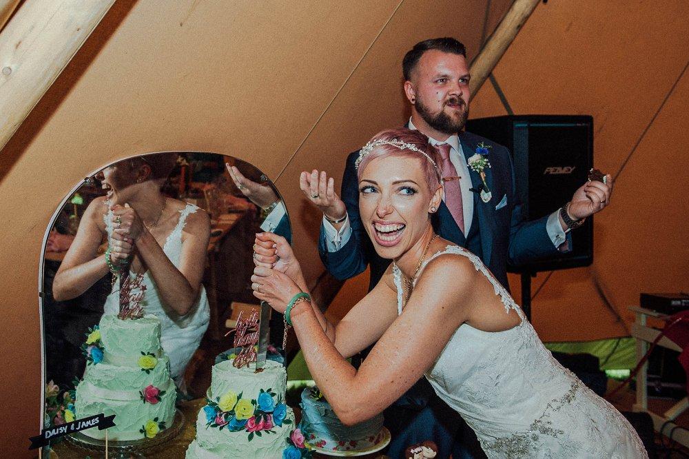 Wyldwoods bride cutting wedding cake photo