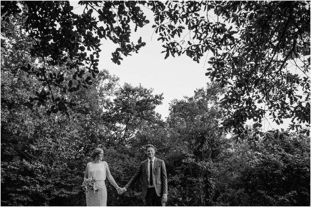 Logis Puygaty bride and groom holding hands under trees