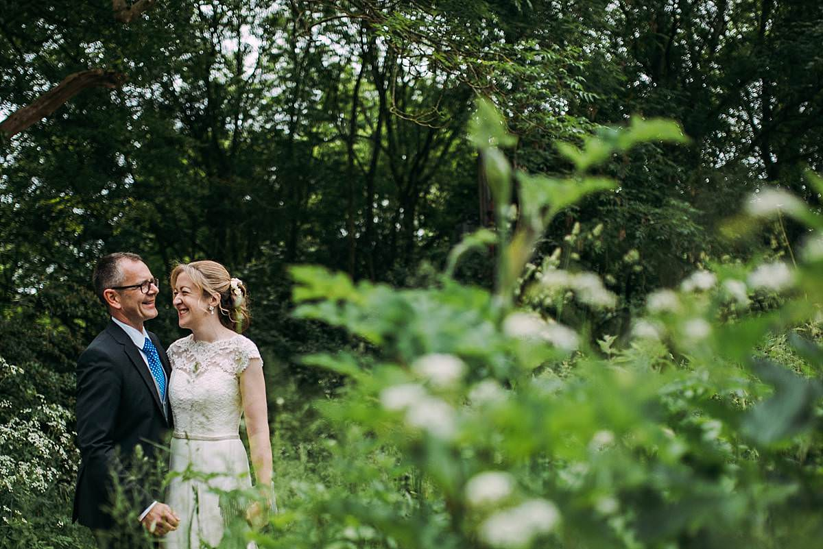 relaxed naturally lit portrait of bride and groom laughing in a forest of green