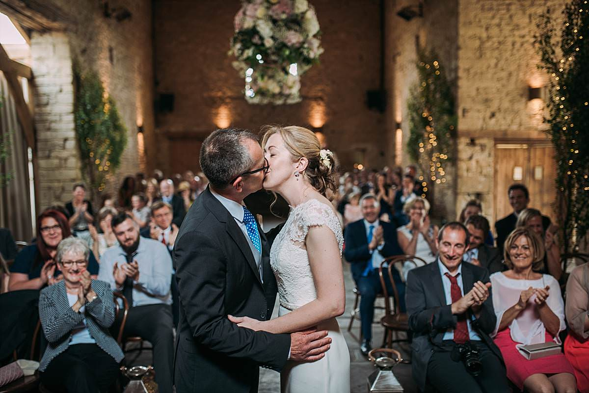 celebratory moment of the first kiss at beautifully decorated Cripps Barn Wedding