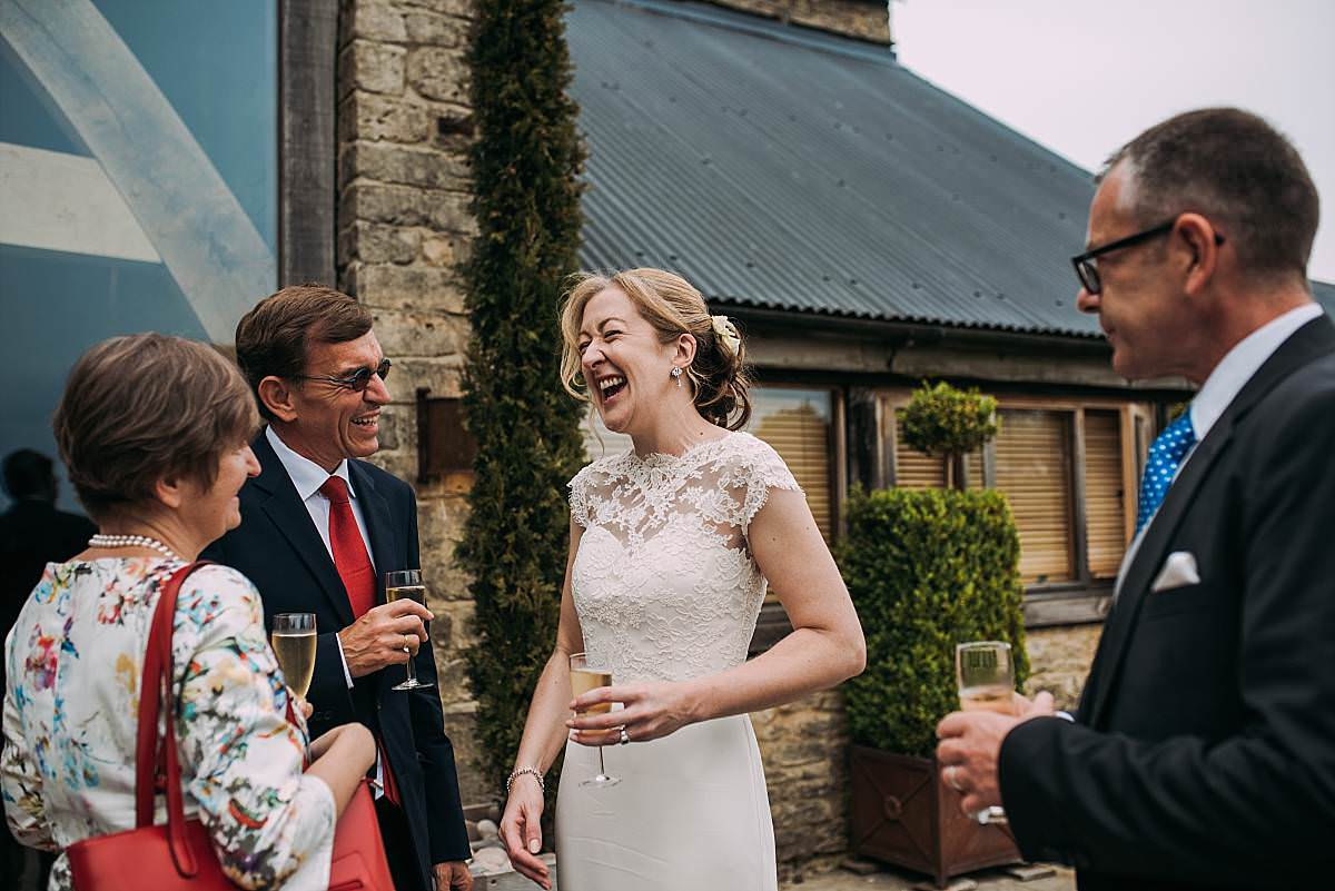 bride laughs hysterically outside with guests as they have a glass of champagne