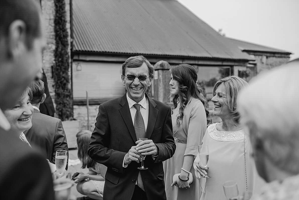 black and white candid portrait of wedding guests enjoying the wedding champagne