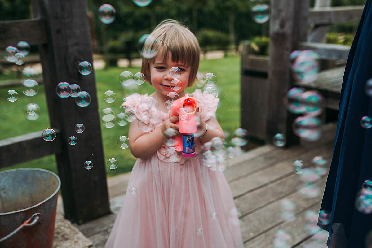 portrait of young flower girl in pink dress playing outside with a bubble gun