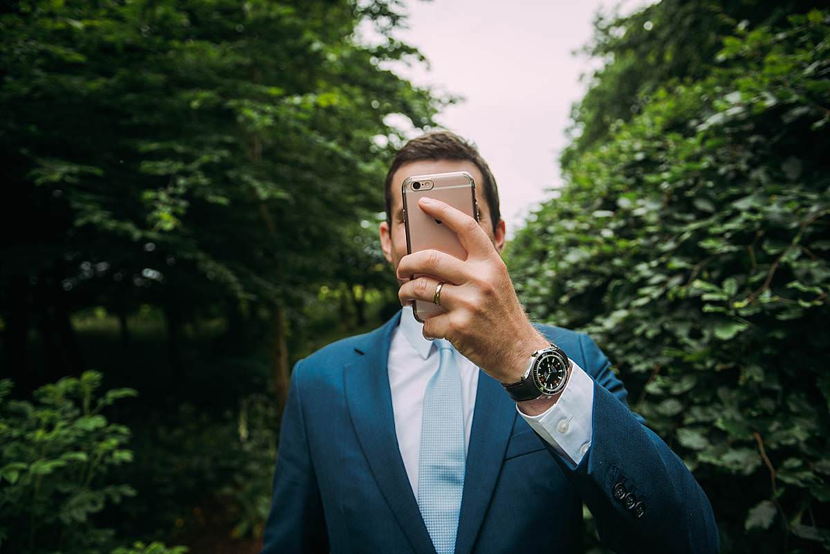 fun images of wedding guest taking a photo on his mobile phone