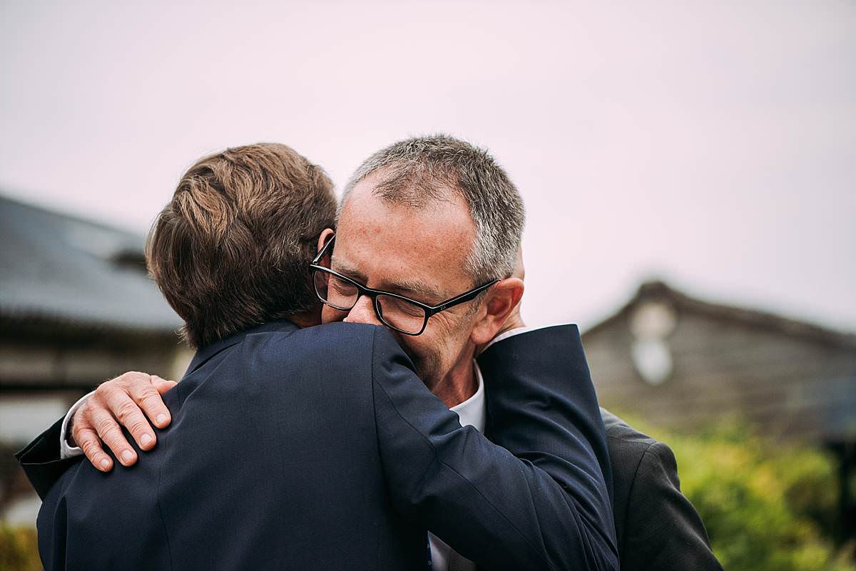 touching embrace between groom and best man