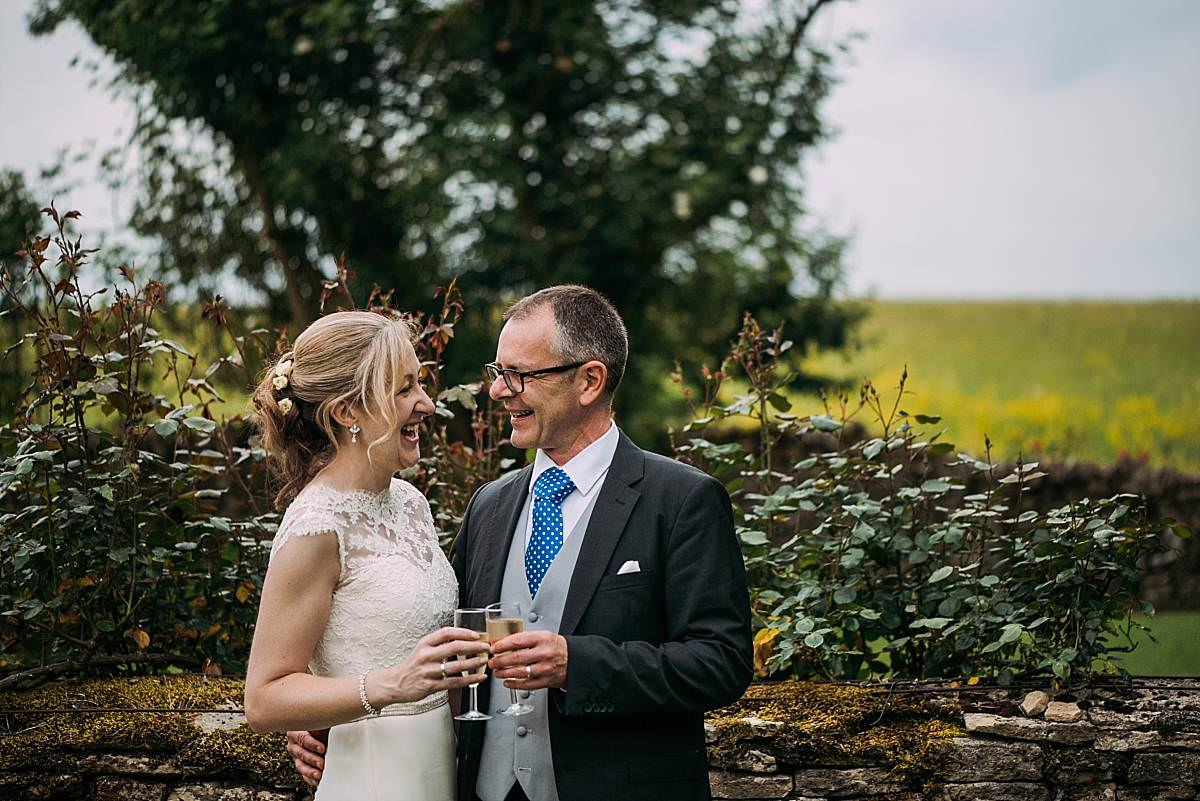 bride and groom share a glass of champagne during their summers day wedding