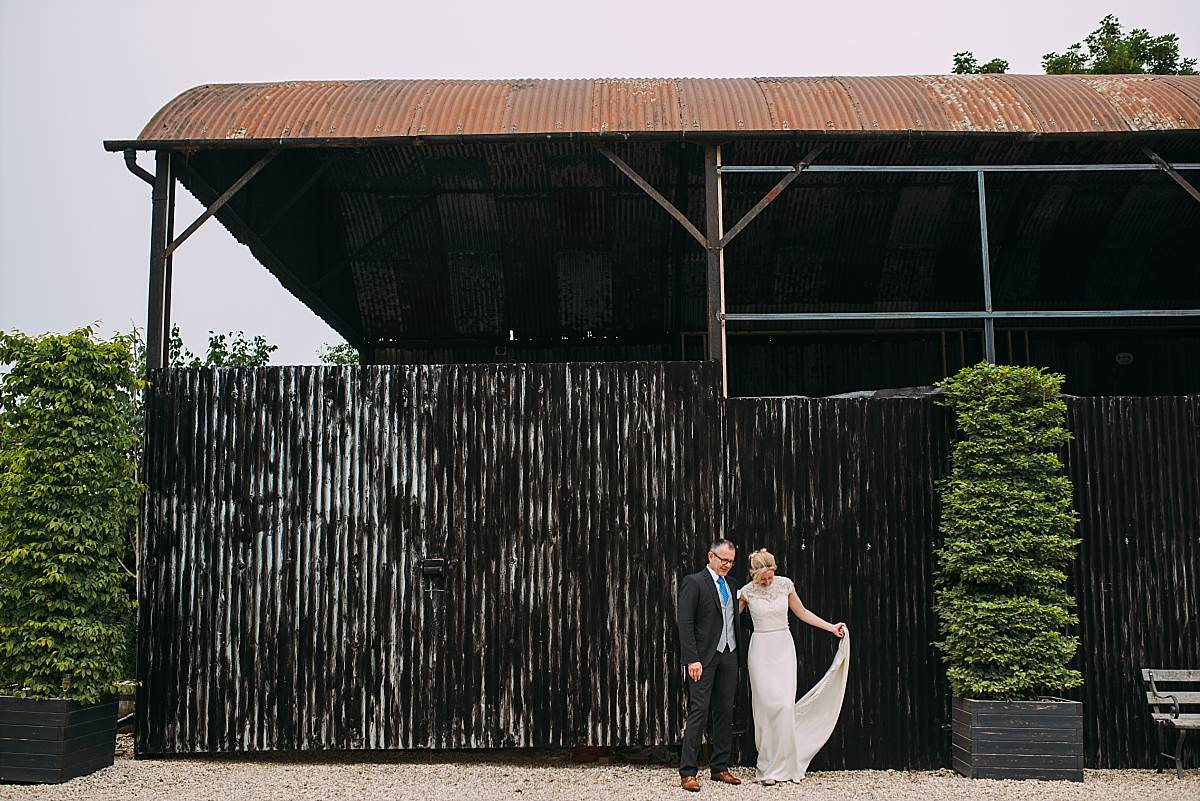 bride and groom stood by old corrugated barns in the Cotswolds