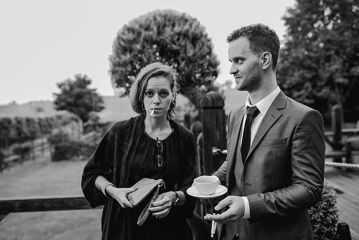candid image of wedding guests outside sharing a cigarette and a cup of tea