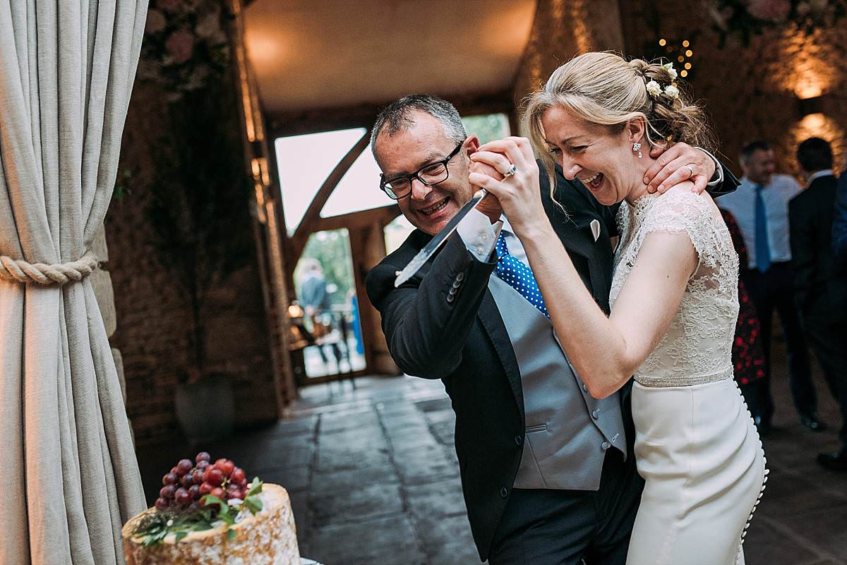 bride and groom playfully cut the wedding cake at Cripps Barn