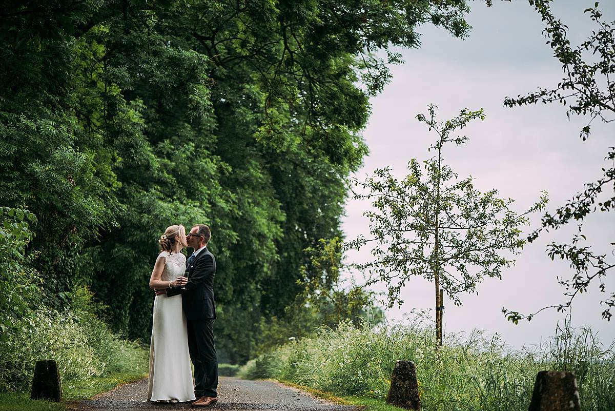 bride and groom kiss on the driveway at Cripps Barn in Gloucestershire