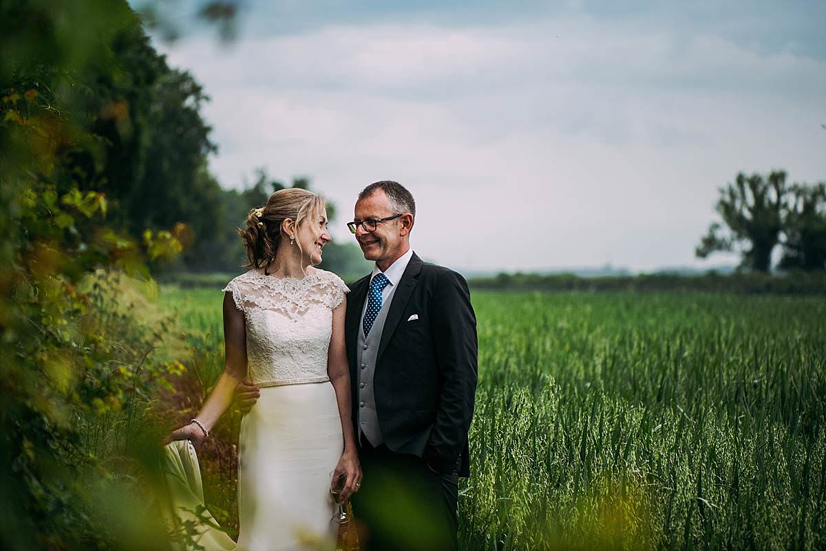 romantic portrait of the bride and groom gazing into each others eyes playfully in a field