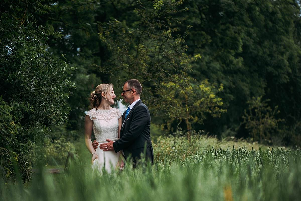 romantic portrait of bride and groom embracing in fields at a Cripps Barn Wedding