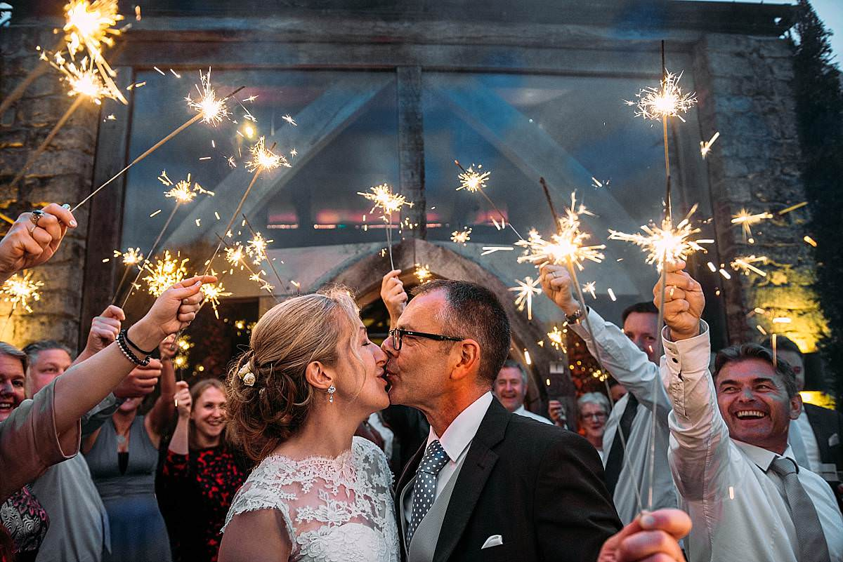 bride and groom kiss as the guests celebrate with sparklers at their Cripps Barn Wedding