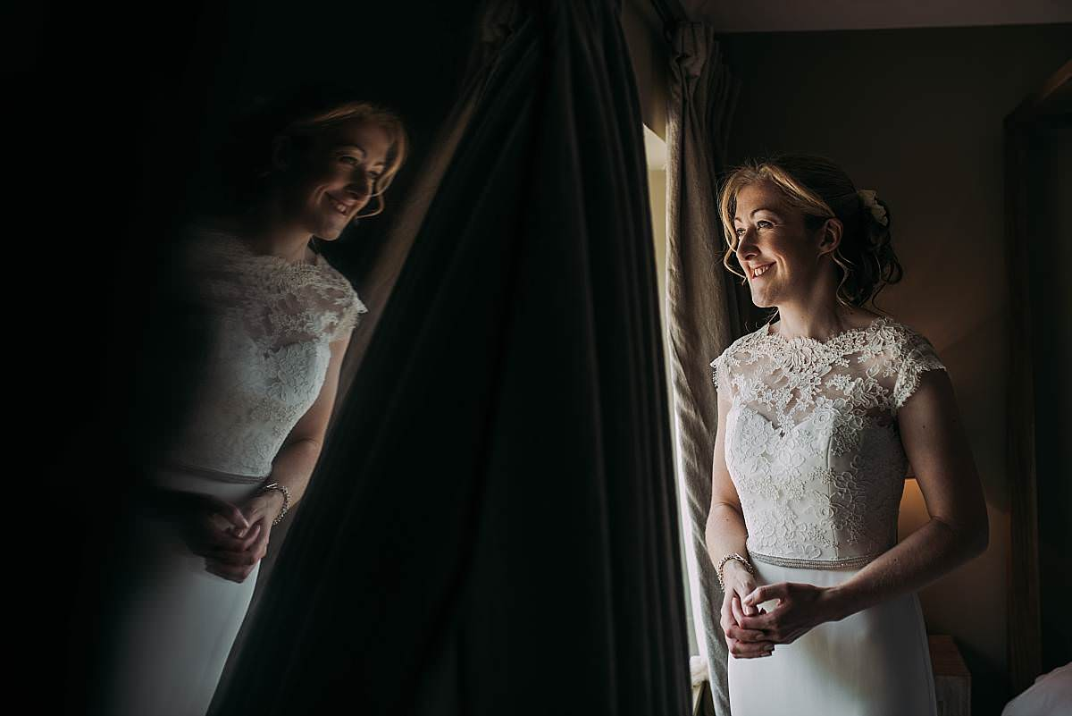 naturally lit portait of happy bride in her wedding dress with window reflection