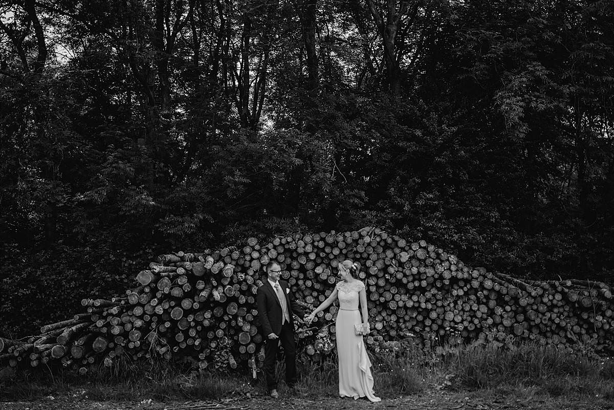 bride and groom laugh with each other holding hands in front of stacked log pile