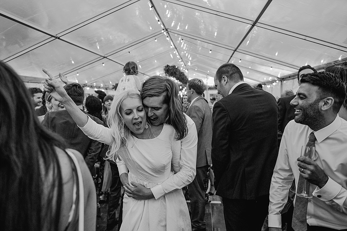 Bride and groom cuddling on dance floor at High Paradise Farm