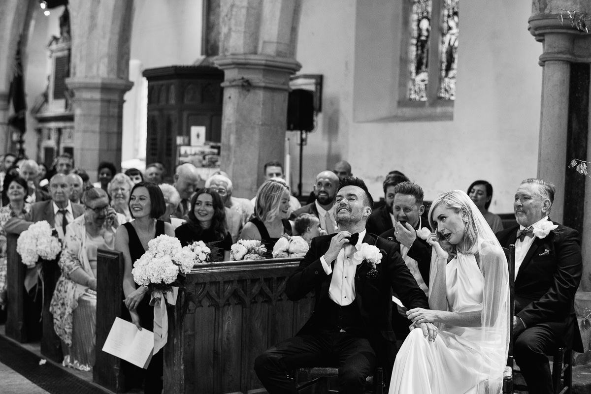 Bride and groom with guests during ceremony at Cranborne church