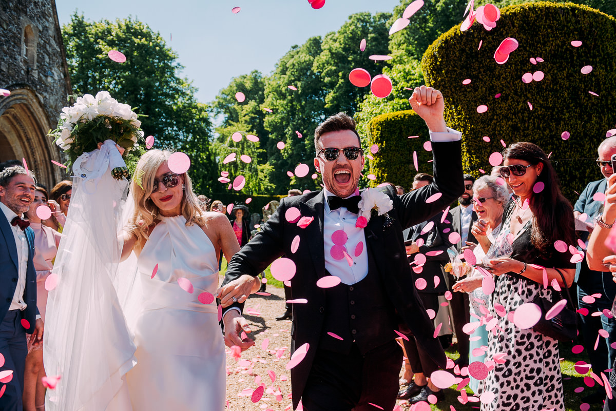 Bride and groom walk through a pink confetti shower after wedding ceremony at Cranborne church