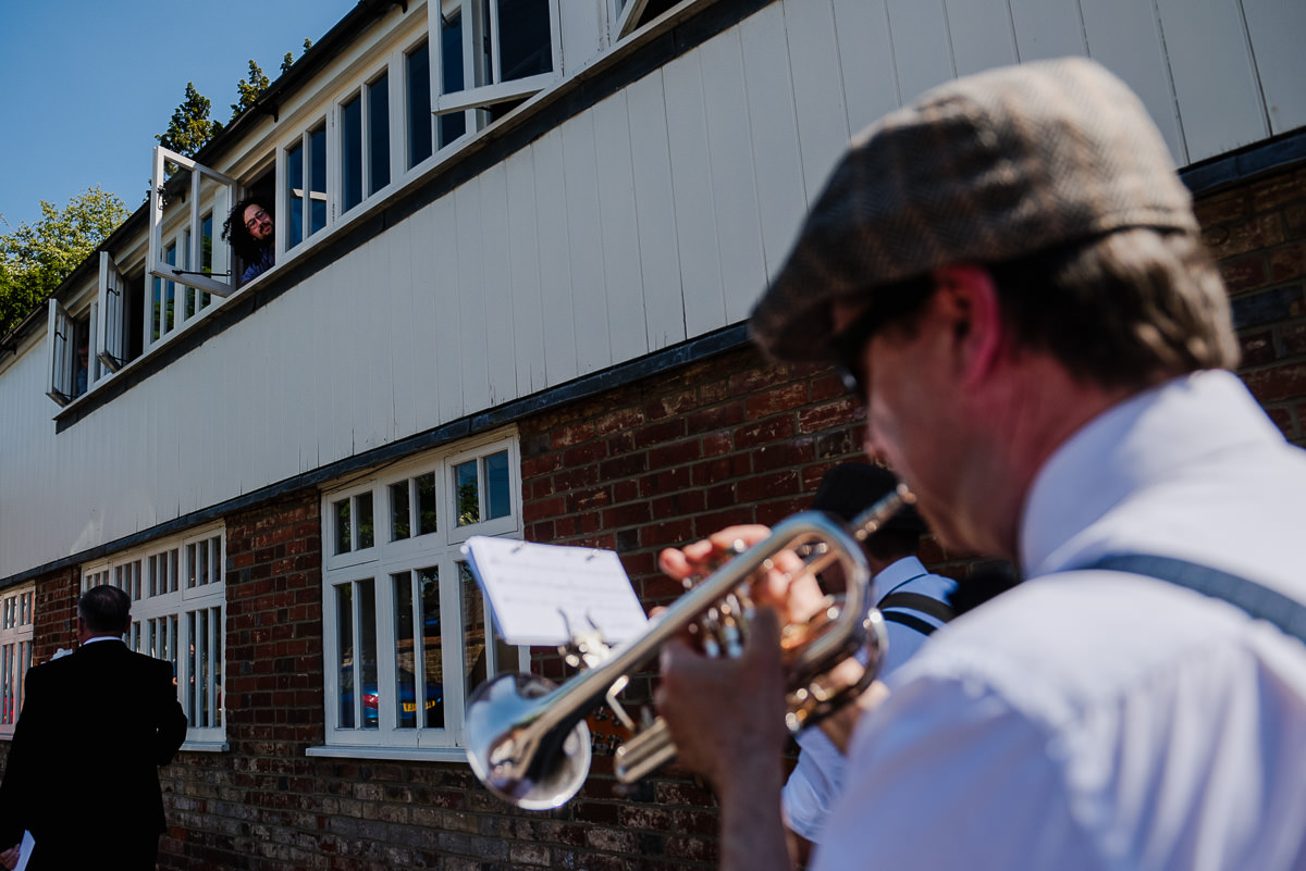 An onlooker out of window as musicians walk to 10 Castle Street wedding venue