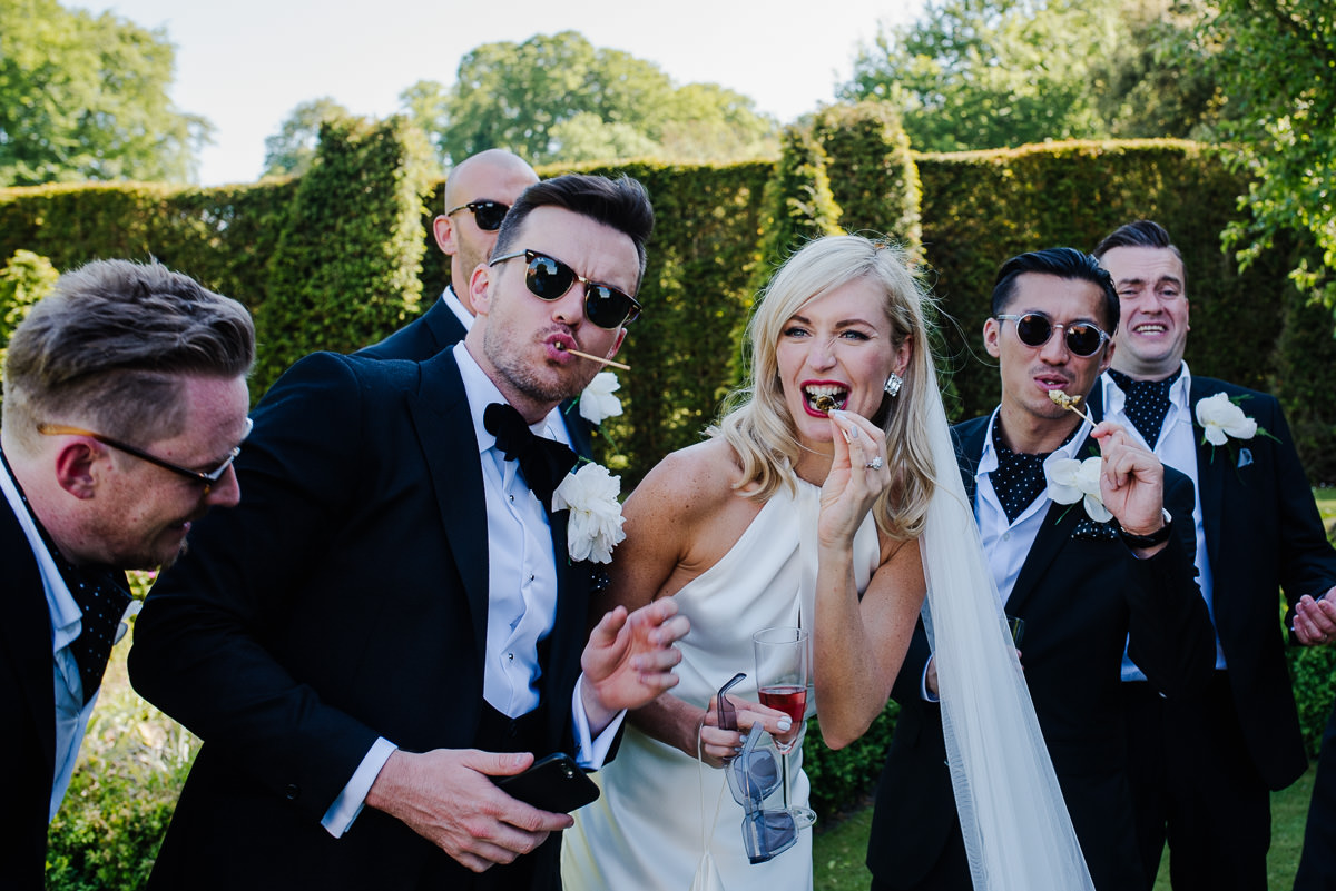 bride and groom eating canapes in garden at 10 Castle street Cranborne wedding photos