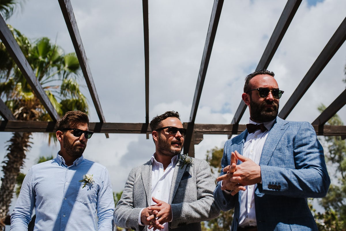 Groomsmen wearing sunglasses  and suits outside Souli beach hotel wedding venue