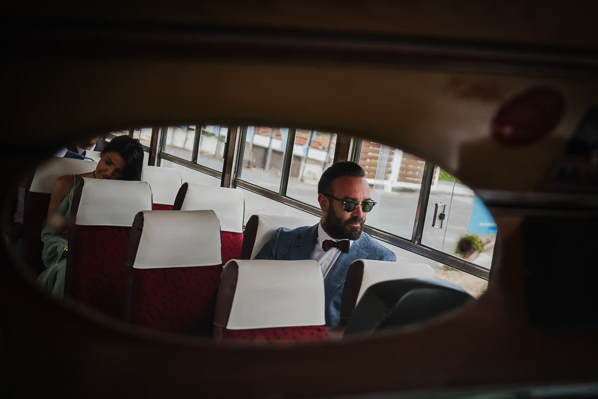 Groom wearing sunglasses in mirror of old bus