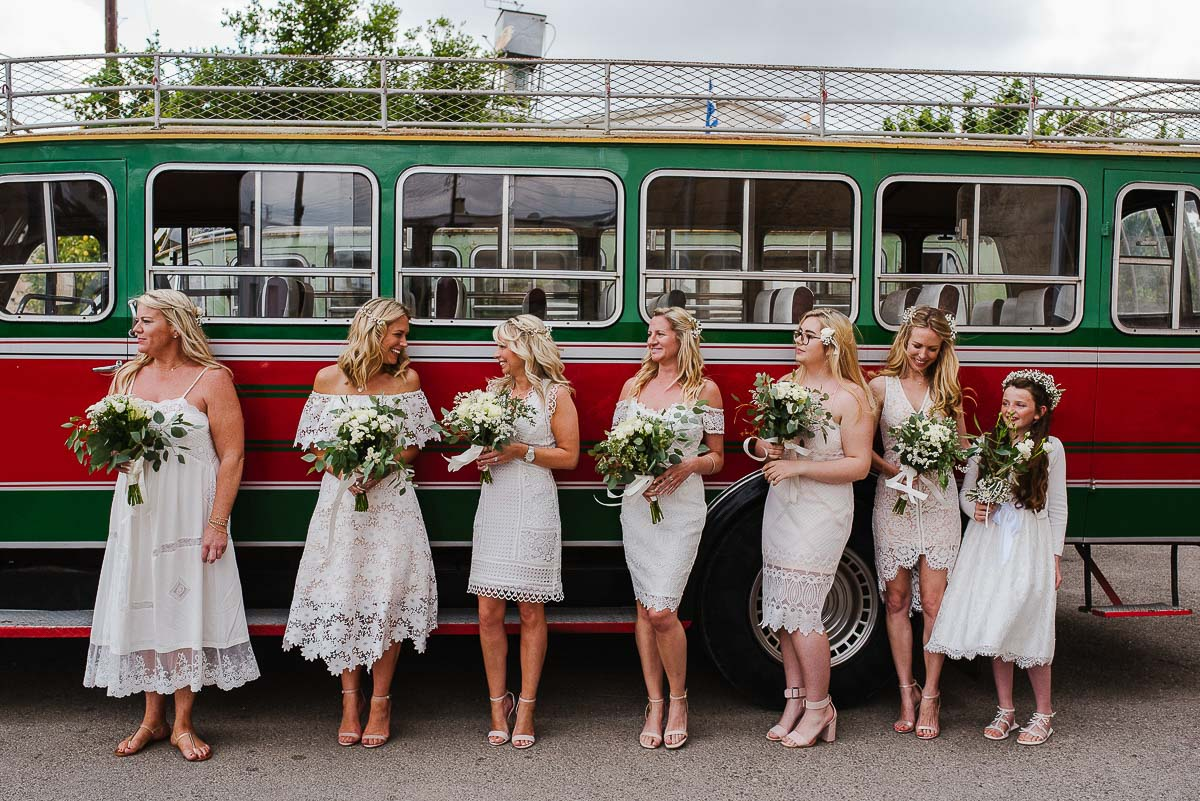 Bridesmaids with matching dresses and flowers standing by traditional bus