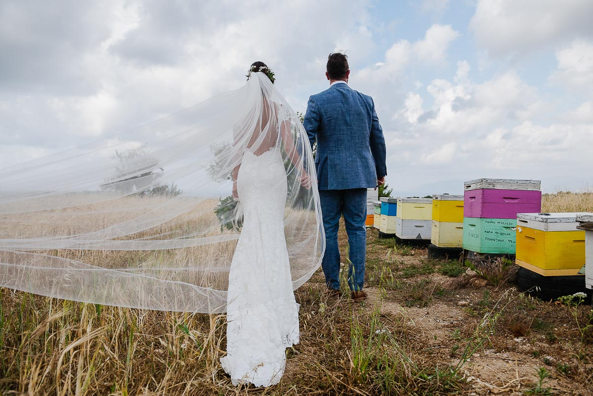 Bride and Groom holding hands with veil blowing in wind during wedding portraits