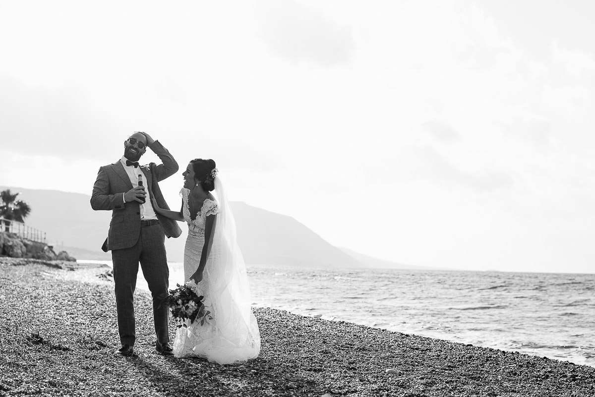 Bride and Groom laughing on the beach during wedding portraits at Souli hotel in Cyprus