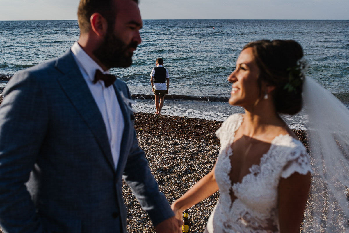 Boy paddling in sea as bride and groom smile at each other on beach in Cyprus