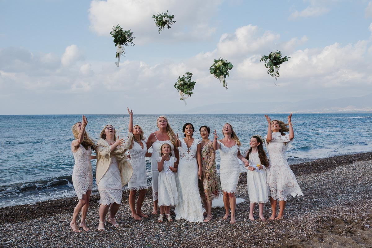 Bridal party throwing bouquets in the air on the beach in Latchi Cyprus