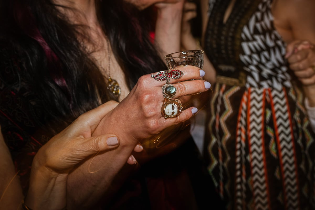 Shots glass and decorative rings on hand of guest at Souli beach hotel wedding venue