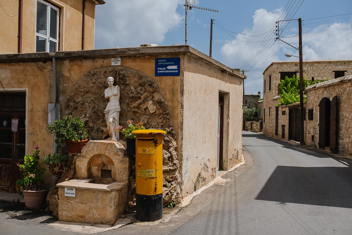 A quiet corner of Polis in Cyprus with Greek statue and yellow letterbox