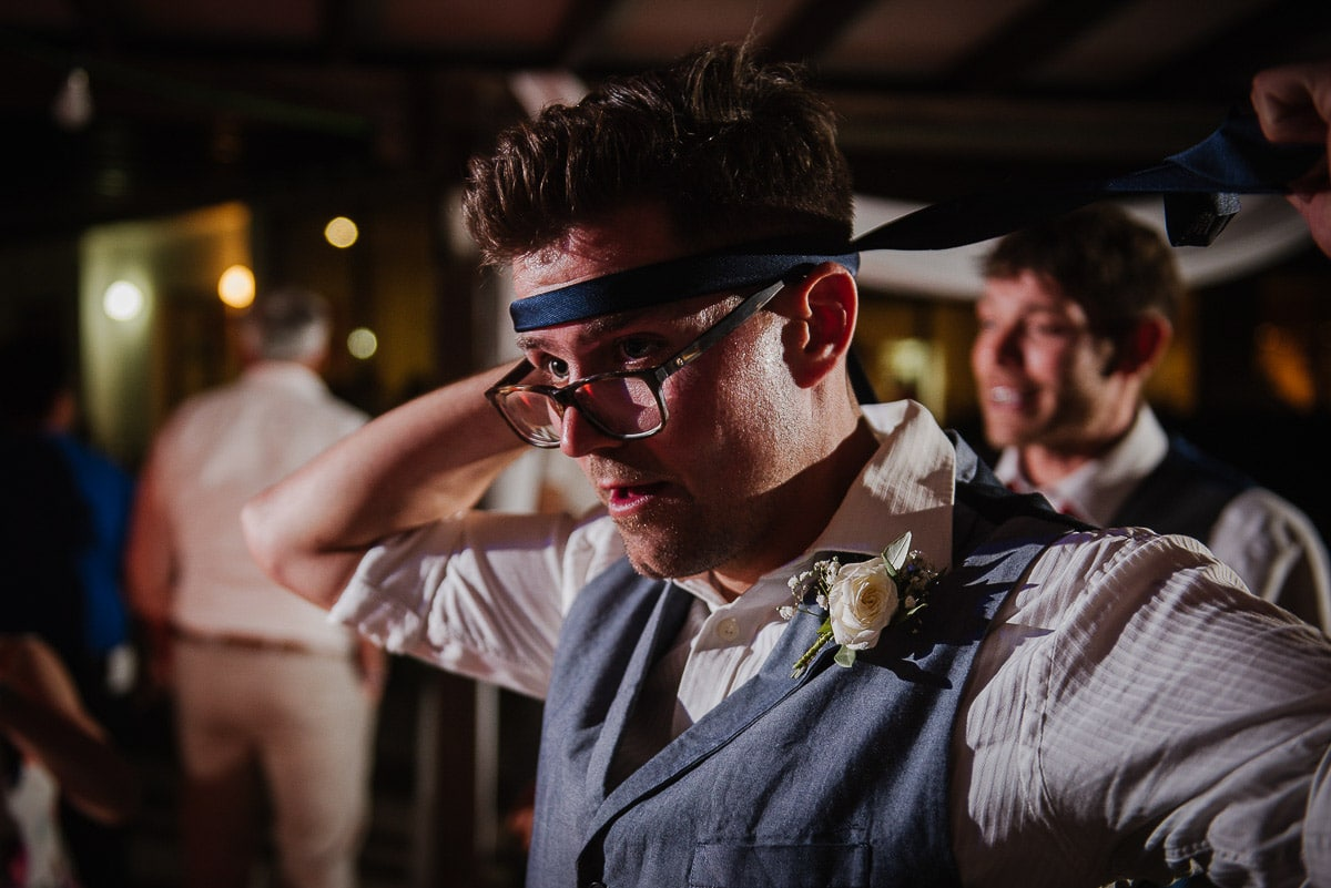 A guest wraps a tie around his head during Souli beach hotel wedding party