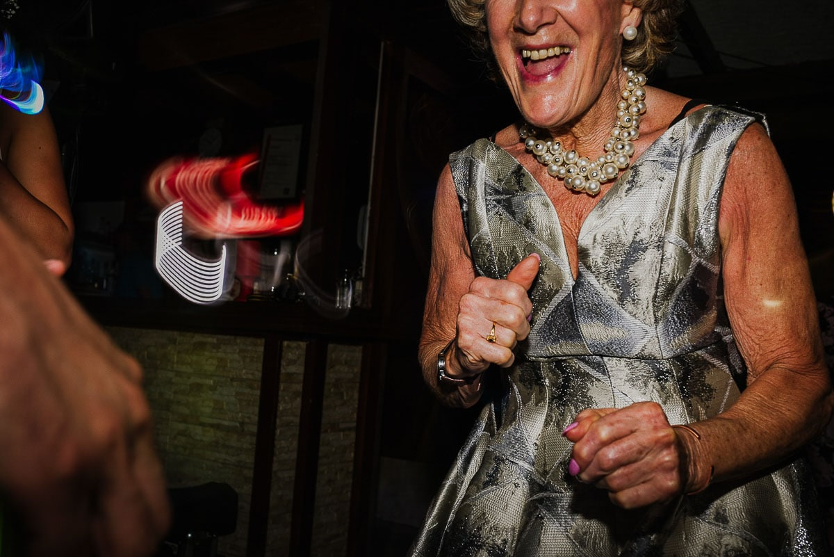 An older lady with shiny dress and necklace dancing during Souli beach hotel wedding part