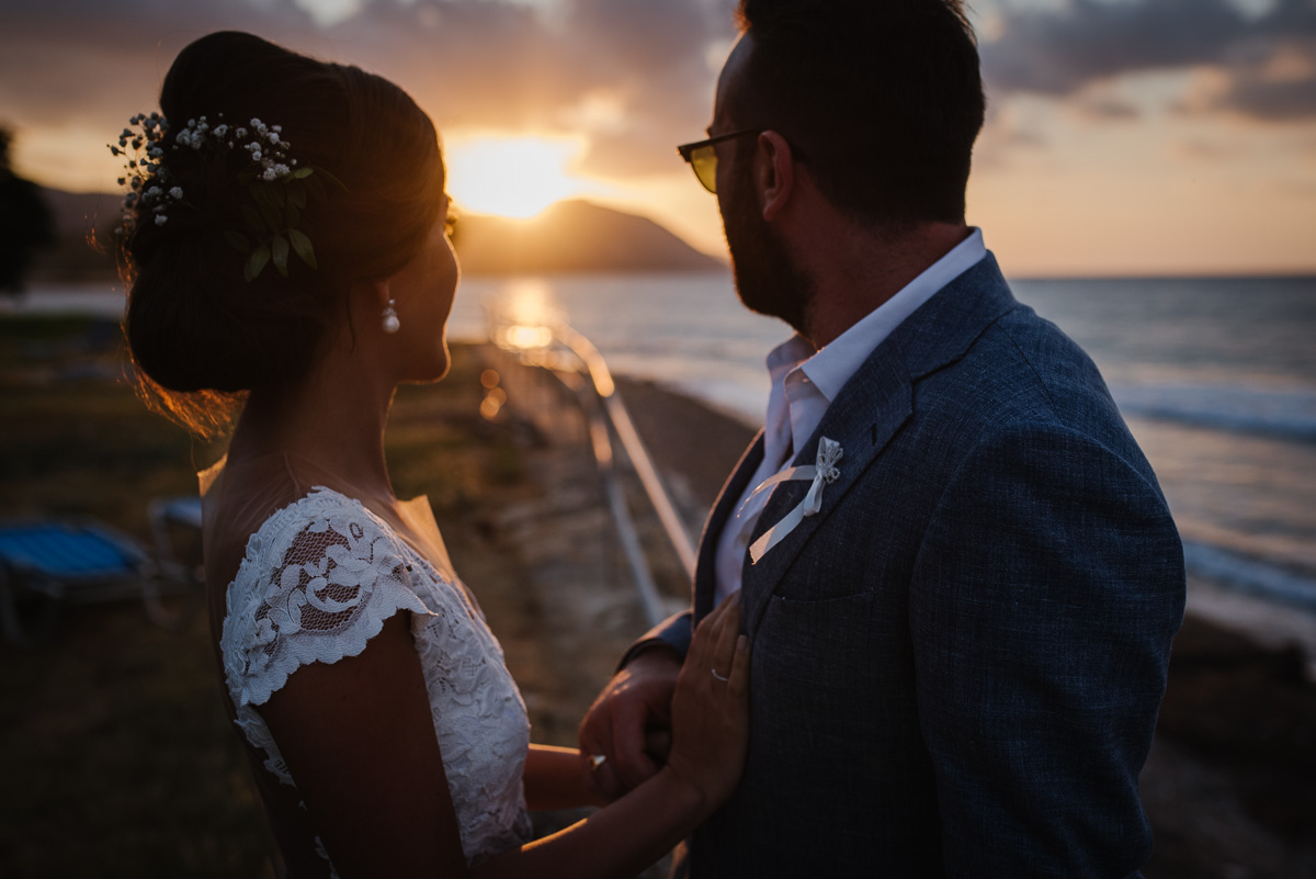Bride and groom watching the sun set during a beach wedding in Cyprus