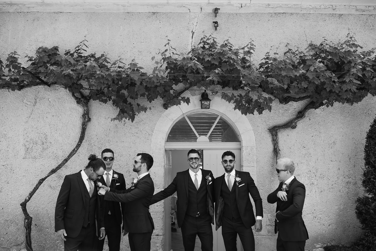 Groomsmen in sunglasses and suits under grapevines in France