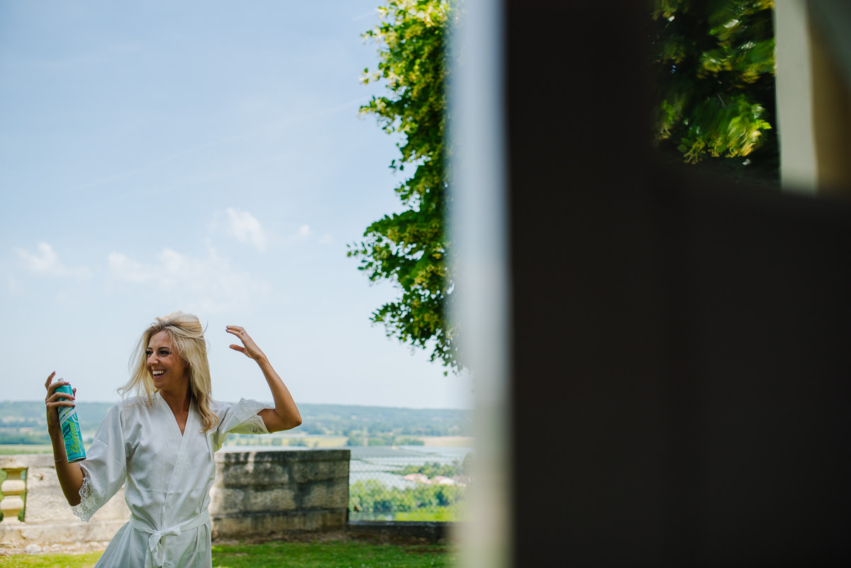 Bride spraying hairspray Chateau Soulac Dordogne wedding photos
