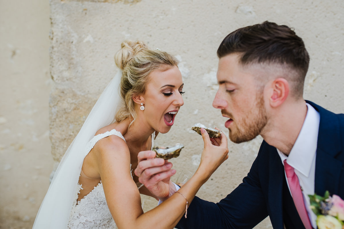 Bride and groom eating oysters at chateau Soulac wedding photos France