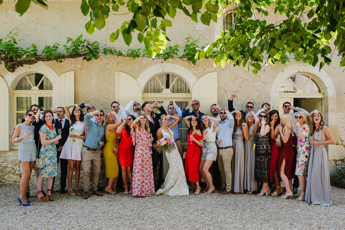 wedding guests all pose with a funny face for the camera