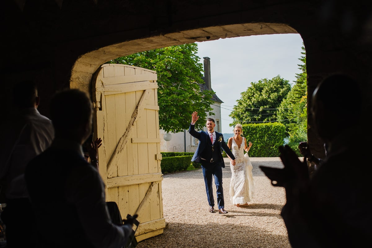 Bride and groom waving to guests Dordogne wedding photos France