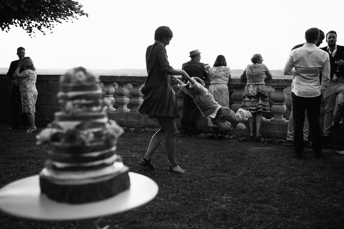 Child being swung behind cake Dordogne wedding photos France