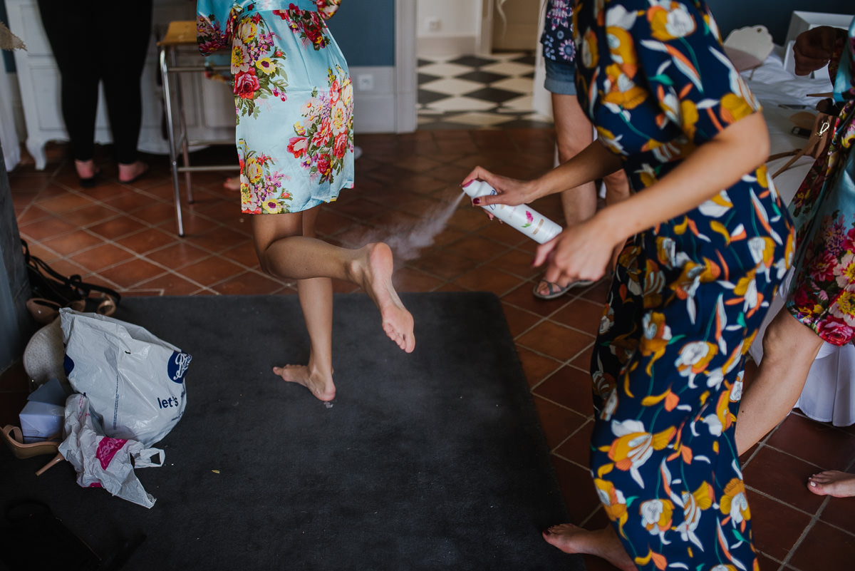 Bridemaids spraying hairspray on feet Chateau Soulac Dordogne wedding photos