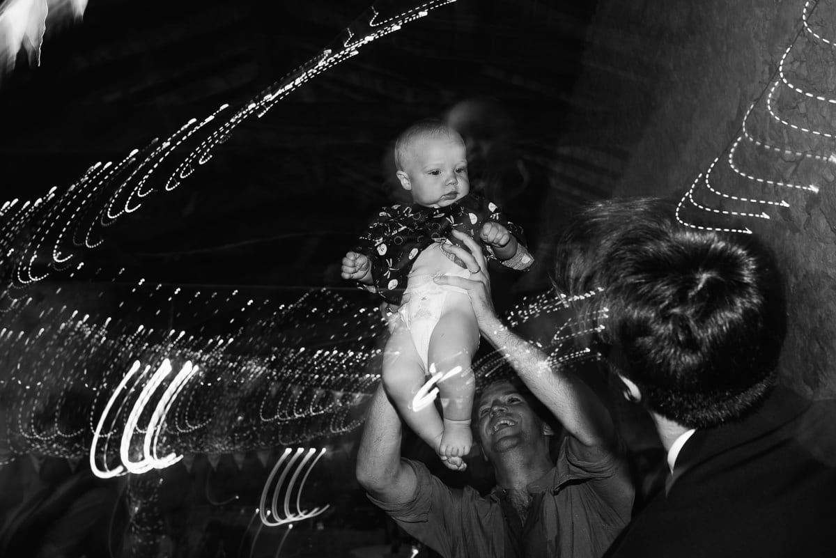 Baby being held aloft chateau Soulac Dordogne wedding photos France