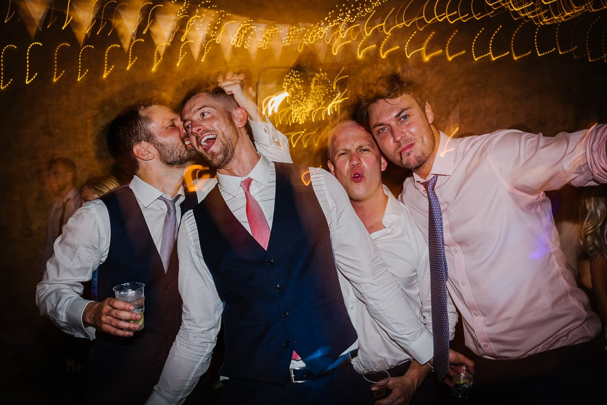 Groom with friends drinking at chateau Soulac Dordogne wedding photos France