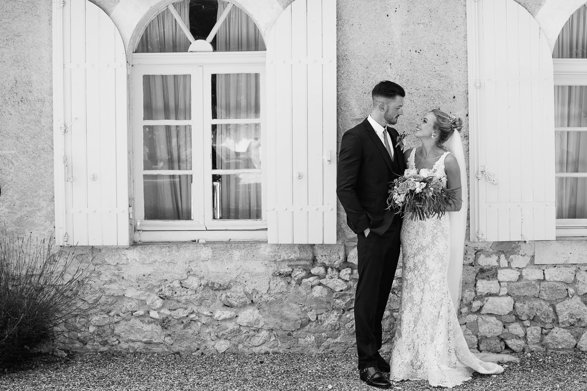 Bride and groom standing beside French shutters Chateau Soulac in Dordogne France