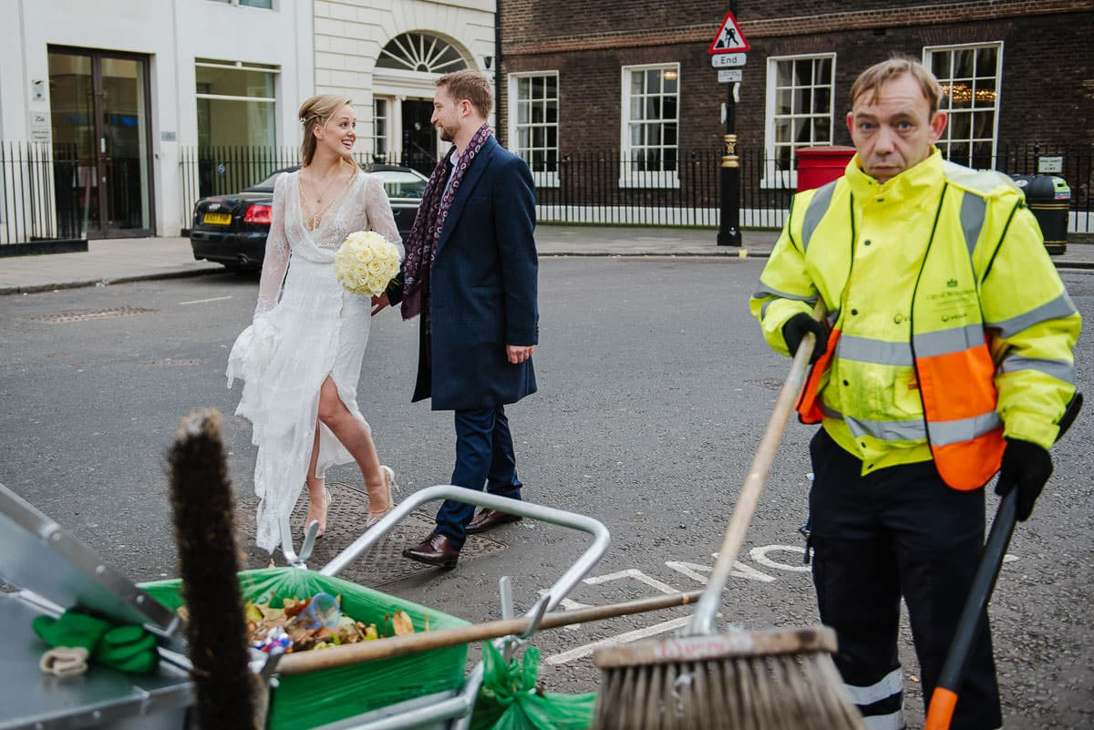 bride and groom take a stroll through London town with bemused litter picker